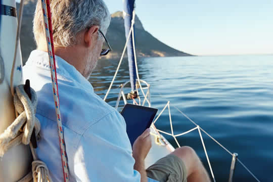 man on yacht looking at McEwen investments on i-pad